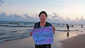 "Women's rights activist, Ye Hiayan (AKA Hooligan Sparrow), holds a sign which reads, ""All China Women's Federation is a Farce. China's Women's Rights are Dead."""